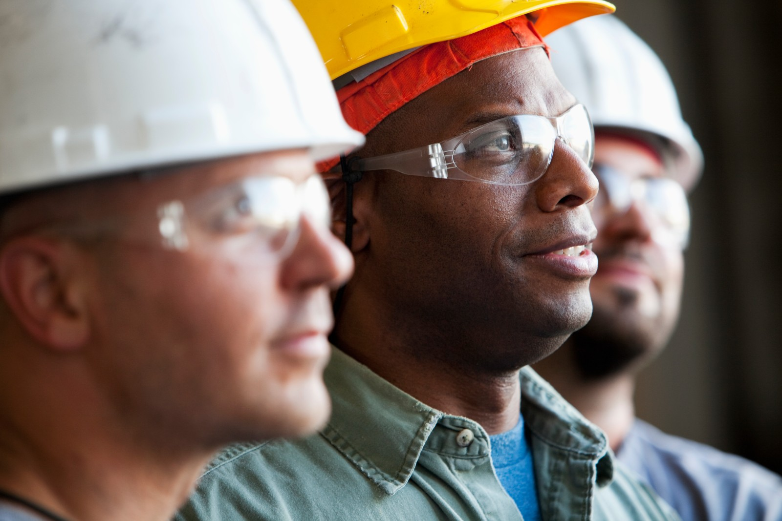 Close up of group of multi-ethnic construction workers wearing hard hats and safety glasses. Focus on African American man (30s).
